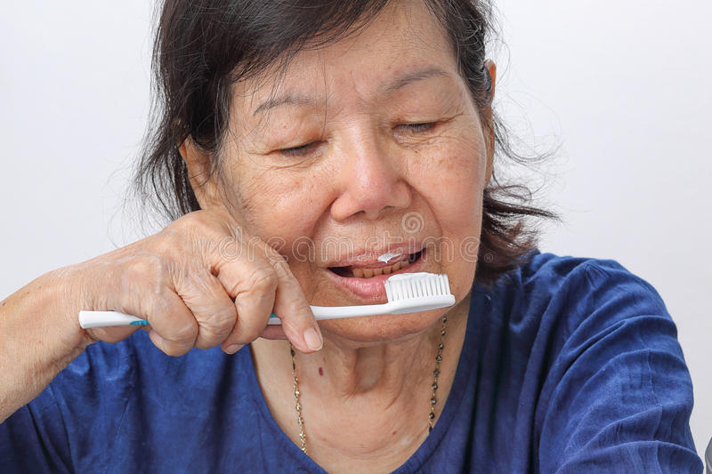 Asian elderly woman trying use toothbrush. stock photography