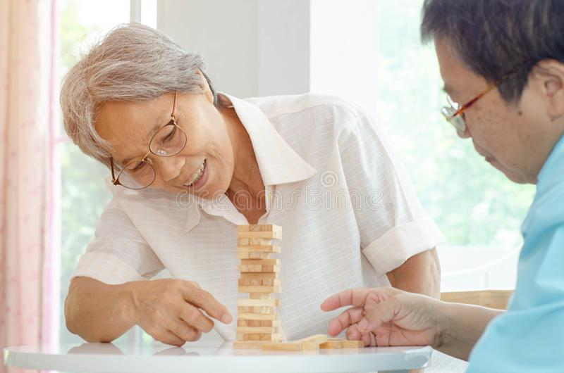 Elderly activities. Asian elderly women Wearing a blue shirt And friend are playing games Have fun in the morning at home in the room royalty free stock image