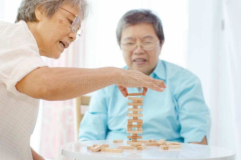 Elderly activities. Asian elderly women Wearing a blue shirt And friend are playing games Have fun in the morning at home in the room royalty free stock photos
