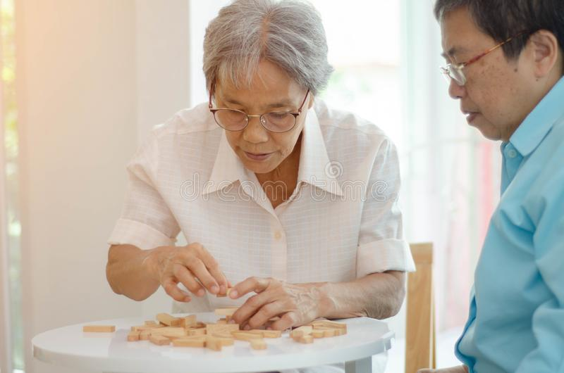 Elderly activities. Asian elderly women Wearing a blue shirt And friend are playing games Have fun in the morning at home in the room stock photos