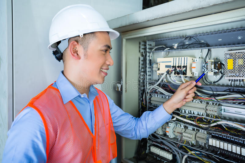 Download Asian Electrician At Panel On Construction Site Royalty Free Stock Photos - Image: 38249478