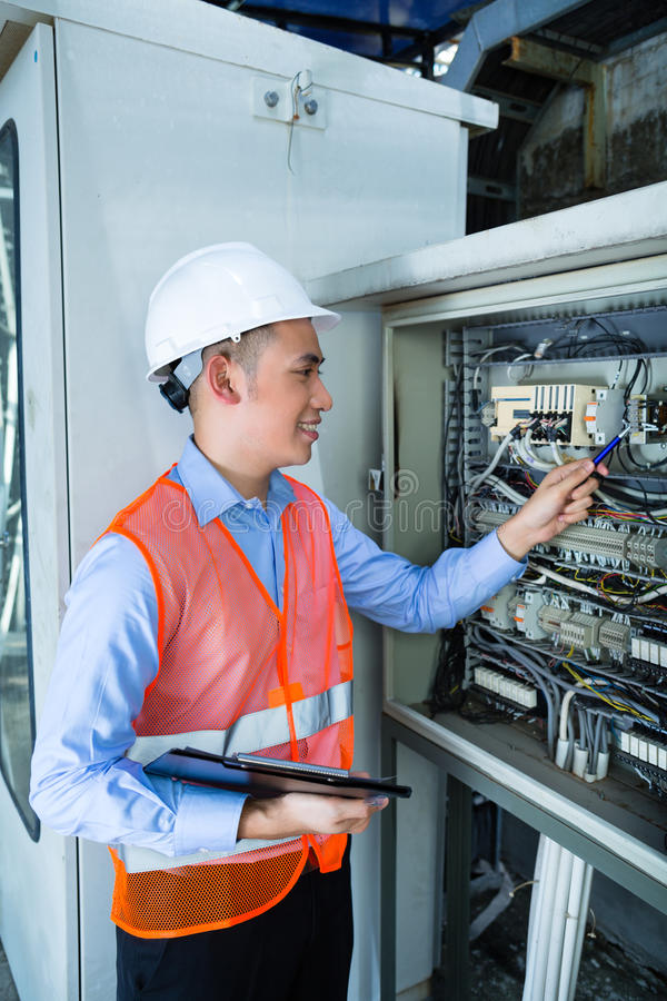 Asian Electrician at panel on construction site. Asian Indonesian Technician or electrician making function test on breaker box or switchbox with power lines on stock photo