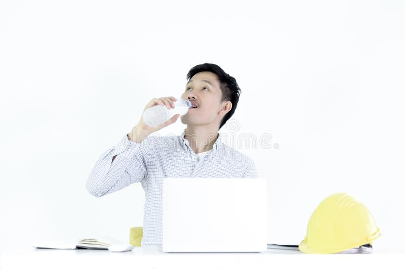 Asian employee engineer salary man sitting at desk and drinking stock photo