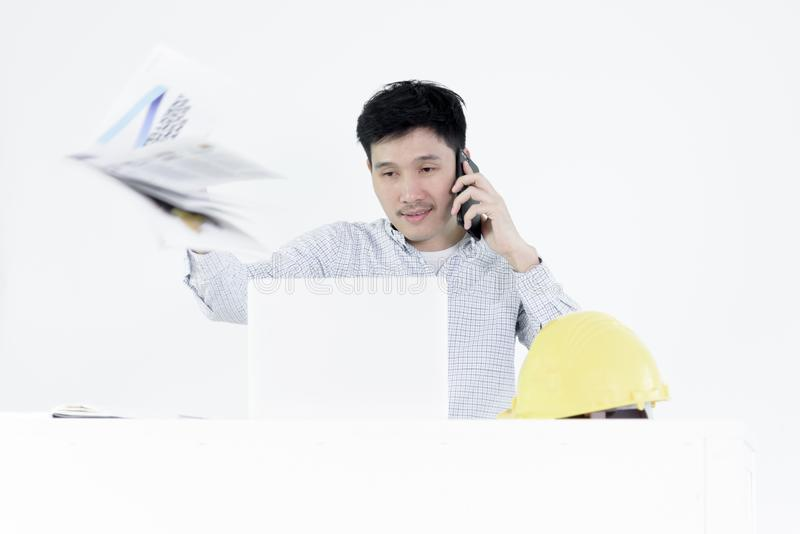 Asian employee engineer salary man sitting at desk throwing book. With feeling angry and upset, isolated on white background stock image