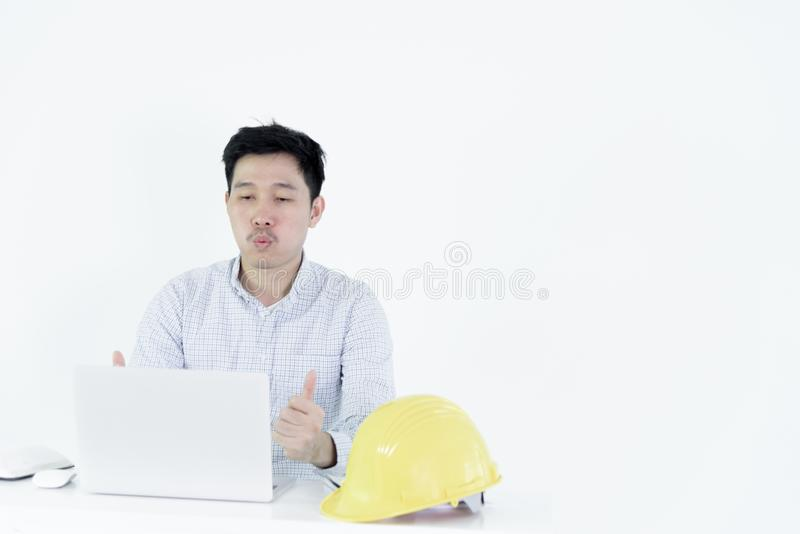 Asian employee engineer salary man sitting at desk and working with feeling successful and victory, isolated on white background. Adult black blue book business stock photo