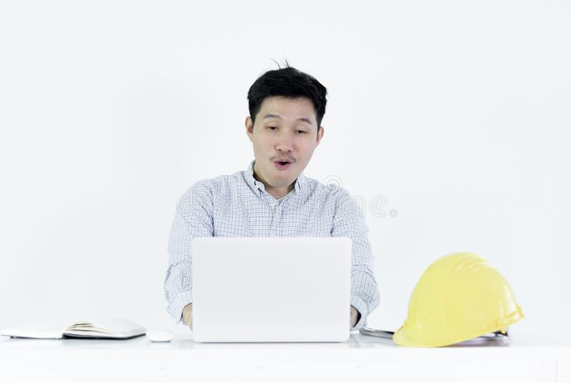 Asian employee engineer salary man sitting at desk and working w. Ith feeling successful and victory, isolated on white background. adult black blue book royalty free stock photo