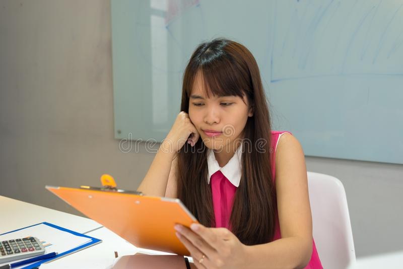 Asian employee reading report with a cute face royalty free stock photo