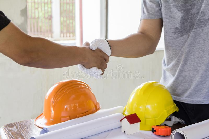 Asian engineer handshaking for teamwork in Interiors design and construction plan. royalty free stock photos