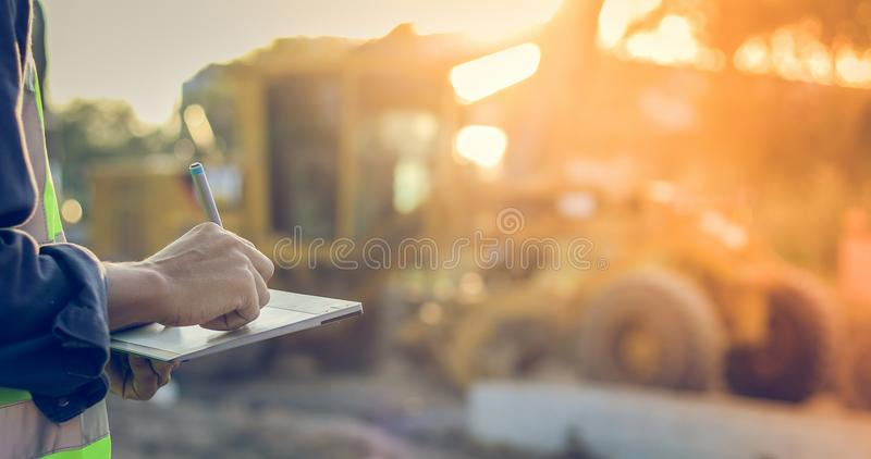 Asian engineer with hardhat using tablet pc computer inspecting royalty free stock image