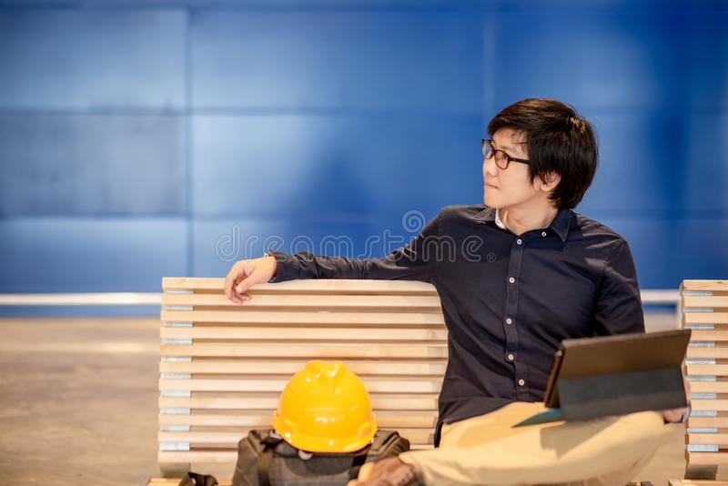 Asian engineer man using digital tablet on bench. Young Asian engineer man using digital tablet while sitting with personal yellow protective safety helmet and royalty free stock images