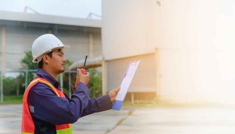 Asian engineer in safety uniform and white helmet holding walkie-talkie and clipboard on blurred industry plant background royalty free stock photos
