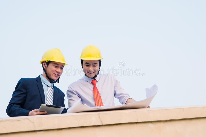 Asian engineer was acting with his secretary on the Business building background.  royalty free stock images
