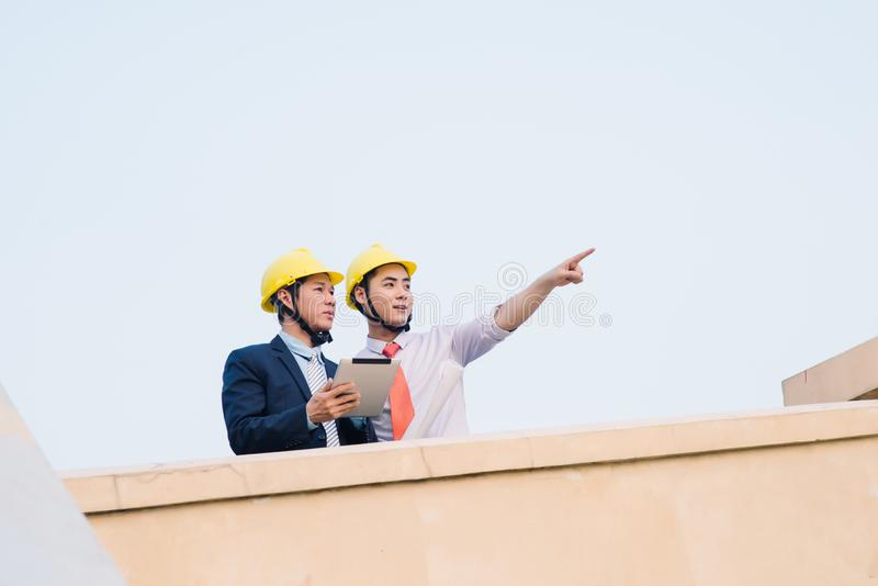 Asian engineer was acting with his secretary on the Business building background stock image