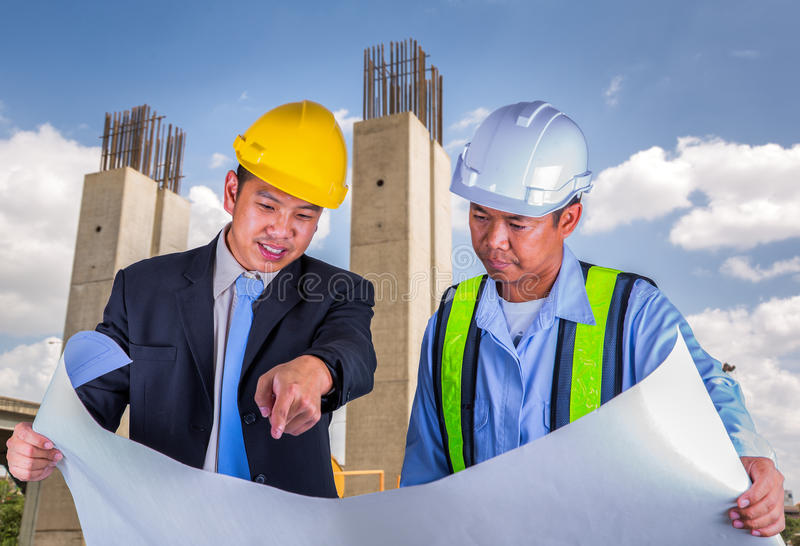 Asian engineer and worker leader discus for drawing detail royalty free stock photography