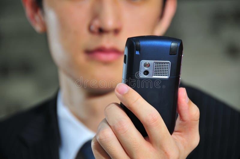 asian executive his mobile reading savvy tech 免版税图库摄影