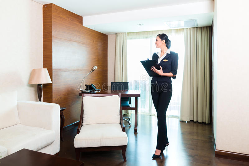 Asian executive housekeeper controlling hotel room royalty free stock image