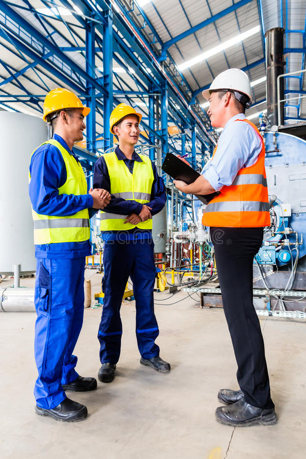 Asian factory worker and engineer as team stock photo