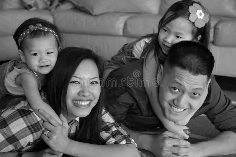Asian family in black and white laughing on floor royalty free stock image