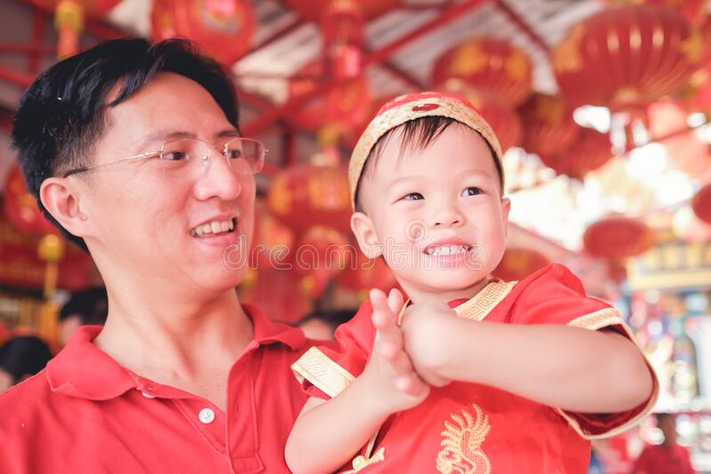Asian family celebrating Chinese new year, Cute little 2 years old toddler boy child in traditional red Chinese suit at local Chin stock image