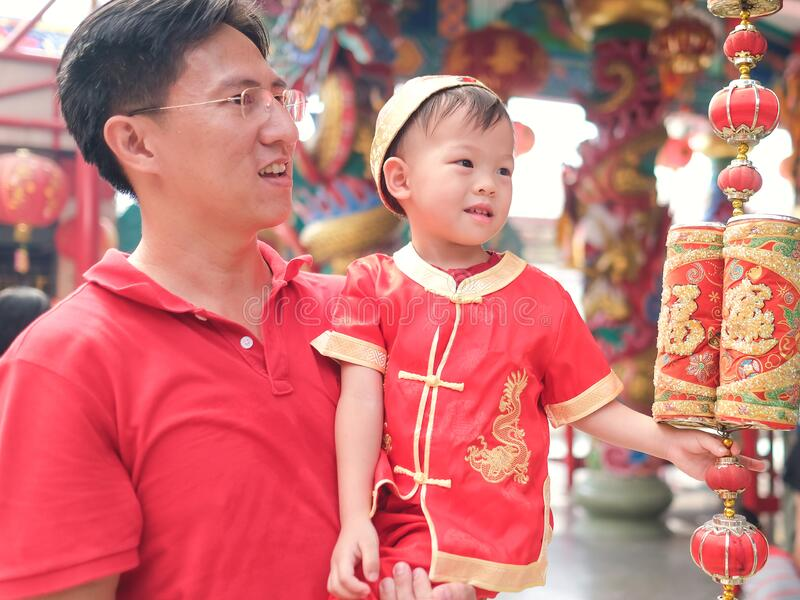 Asian family celebrating Chinese new year, Cute little 2 years old toddler boy child in traditional red Chinese suit at local Chin royalty free stock photos