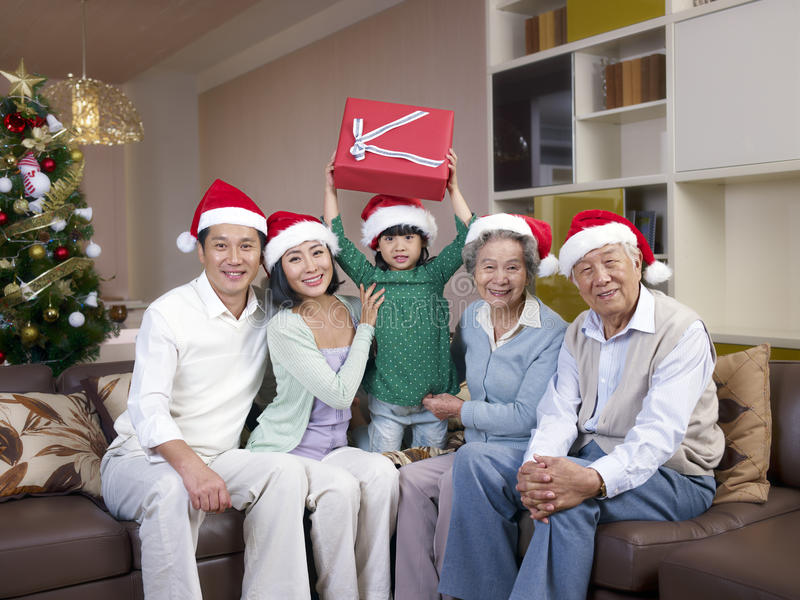 Asian family with christmas Hats. Home portrait of an Asian family with Christmas hats and gifts royalty free stock photos