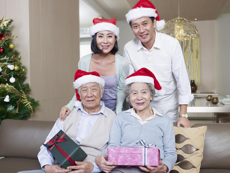 Asian family with christmas hats. Portrait of an Asian family with Christmas hats and gifts stock images