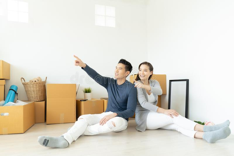 Asian family couple sitting on floor in new apartment with moving boxes, pointing up into the air and smiling with dreaming about stock photos