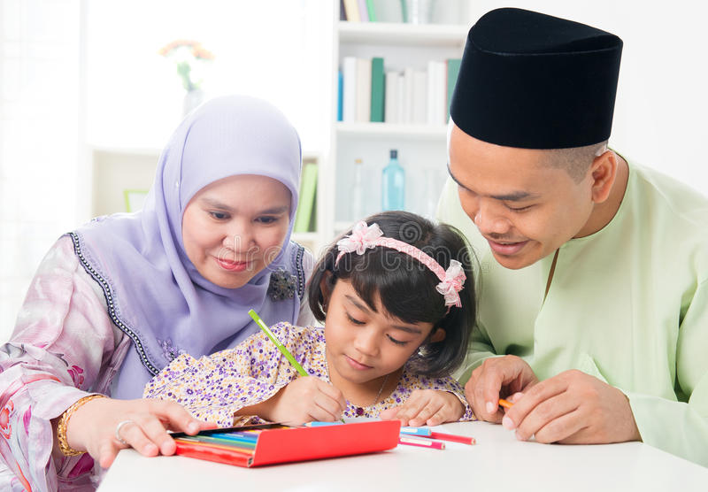 Asian family drawing and painting. Southeast Asian family drawing and painting picture at home. Muslim family lifestyle. Happy smiling parents and child stock photos