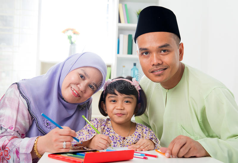 Asian family drawing. Southeast Asian family drawing and painting picture at home. Malay Muslim family lifestyle. Happy smiling parents and child royalty free stock photos