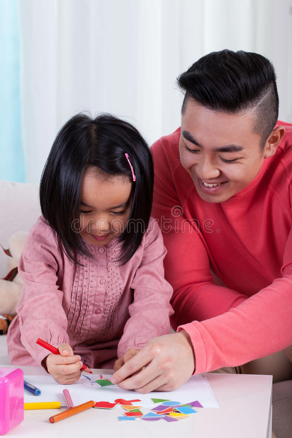 Asian family drawing together. Vertical view of asian family drawing together stock photo