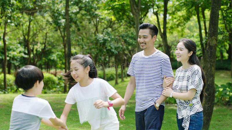 Asian family enjoying summer weekend in park walking & smiling stock photography