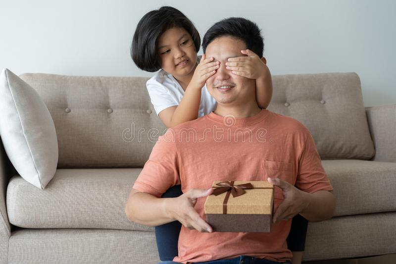 This Asian family has  father and daughter. A little girl  Presenting a birthday gift box to father they are happy in their home royalty free stock photos