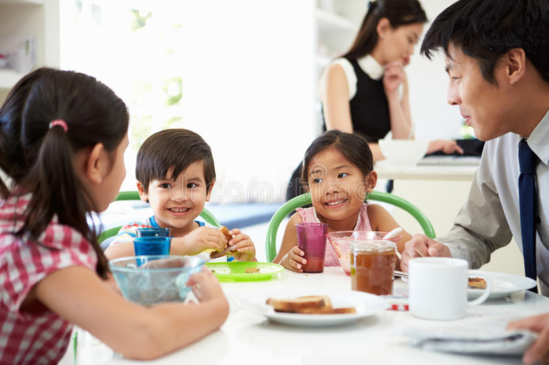 Asian Family Having Breakfast Before Husband Goes To Work. Sitting At Table Smiling royalty free stock image