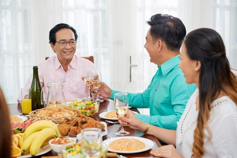 Content people toasting at family dinner royalty free stock images