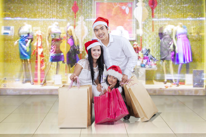 Asian family kneeling at the mall. Cheerful asian family kneeling at shopping center while wearing christmas hat and holding shopping bags royalty free stock photo