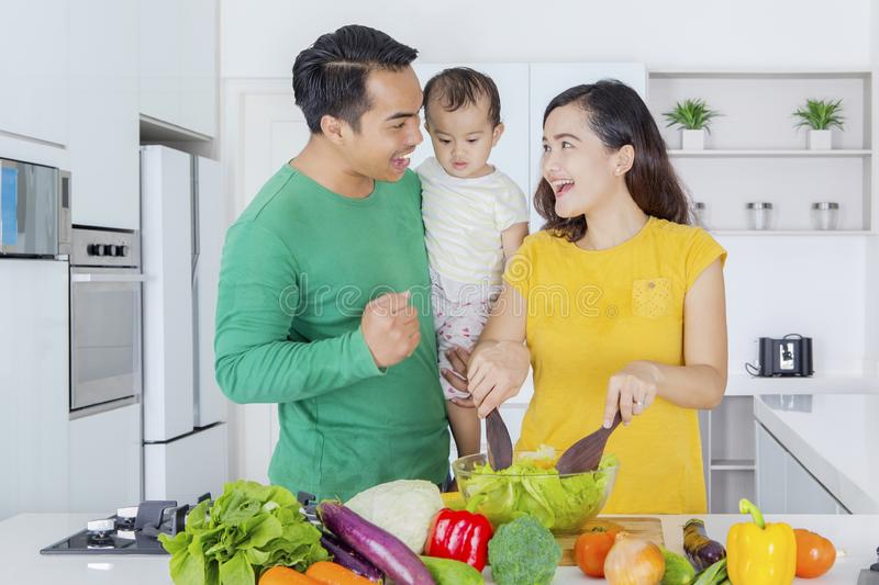 Asian family making vegetable salad in kitchen royalty free stock photography