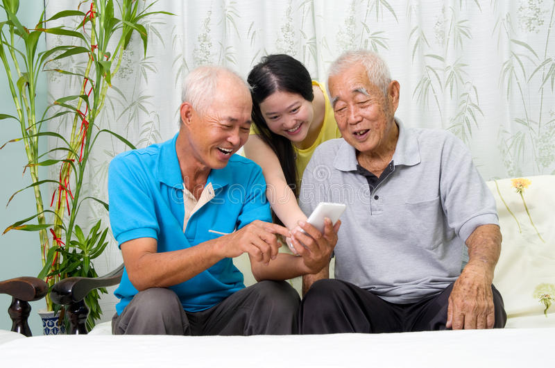 Asian family. Modern technology, age and people concept. Asian family using smart-phone, self photographing. Family living lifestyle at home royalty free stock image