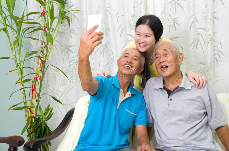Asian family. Modern technology, age and people concept. Asian family using smart-phone, self photographing. Family living lifestyle at home stock photography