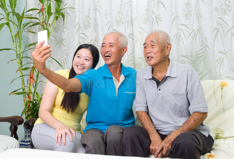 Asian family. Modern technology, age and people concept. Asian family using smart-phone, self photographing. Family living lifestyle at home stock photo