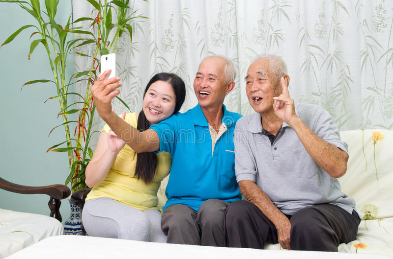 Asian family. Modern technology, age and people concept. Asian family using smart-phone, self photographing. Family living lifestyle at home stock image