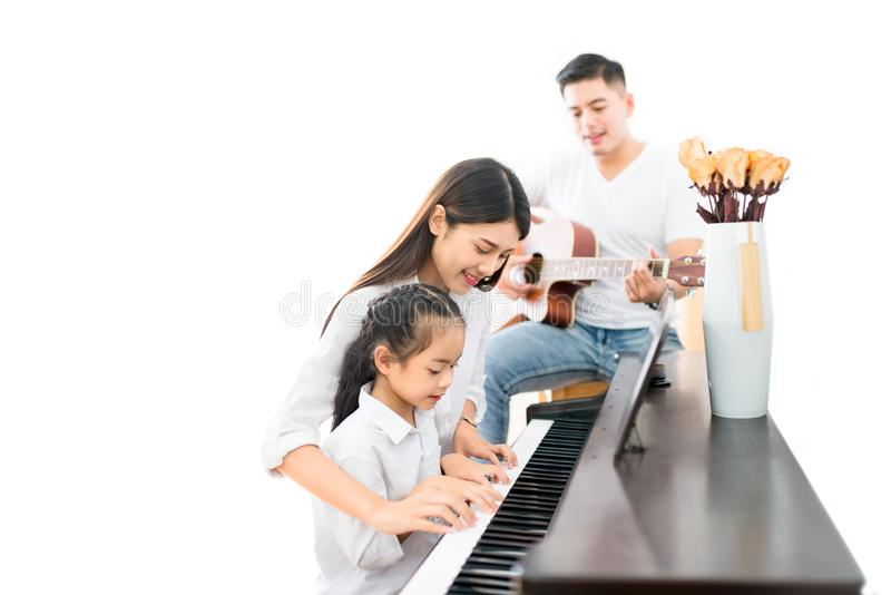Asian family, mother and daughter playing Piano,father playing. Guitar in family band at home, concept for family relationship stock photography