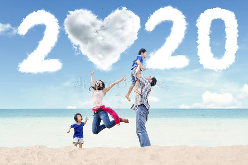 Asian family with number 2020 on beach royalty free stock photo