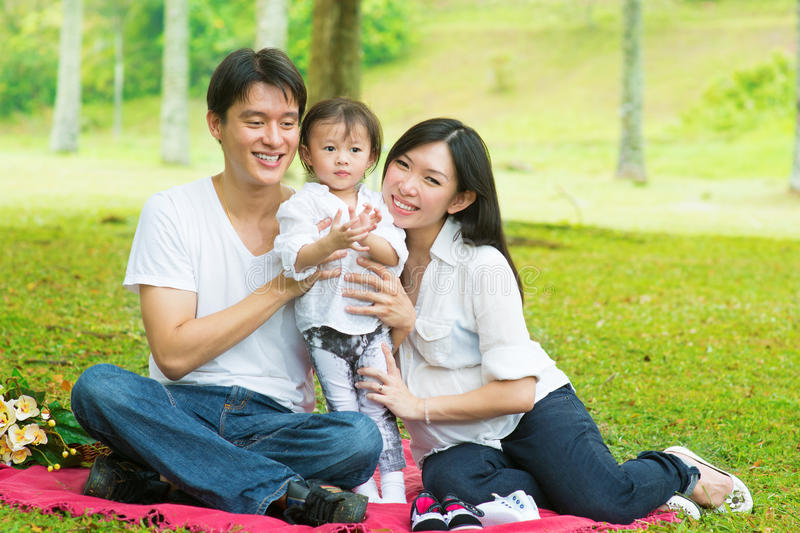 Asian family outdoor picnic. Happy Asian family outdoor activity. Parents and daughter having , picnic on garden green lawn royalty free stock image