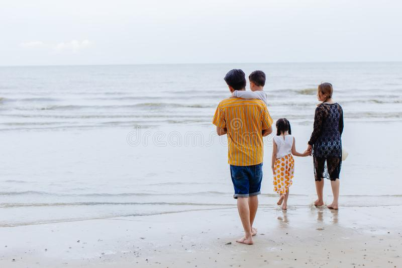 Asian family parents with daughter and son walking at sea beach for summer vacation with space for text royalty free stock photos