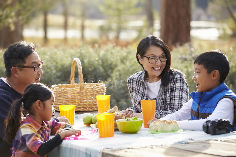 Asian family at a picnic table looking at each other stock images