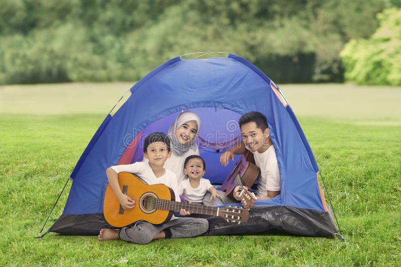 Asian family playing guitars in the tent royalty free stock photo