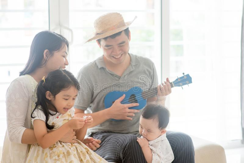 Asian family playing music instrument. Parents and children singing and playing music instruments together. Asian family spending quality time at home, natural stock photo