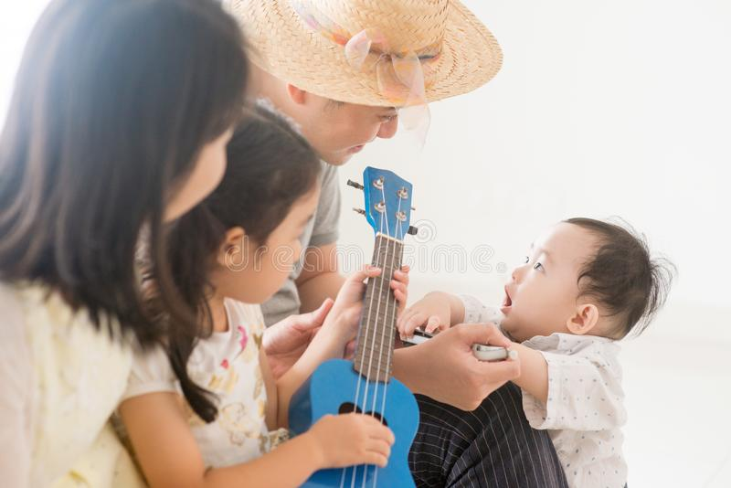 Asian family playing ukulele and harmonica at home. Parents and children playing music instruments together. Asian family spending quality time at home, natural royalty free stock image