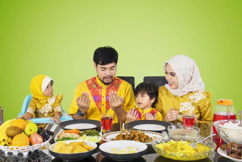 Asian family praying before their break fast stock image