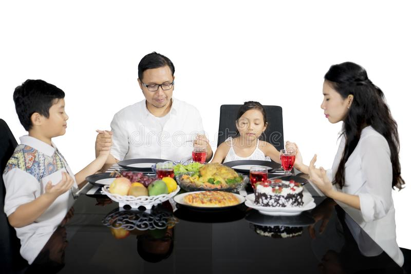 Asian family praying together before having meals. Asian family holding hands to each other while praying together before having meals, isolated on white stock photos